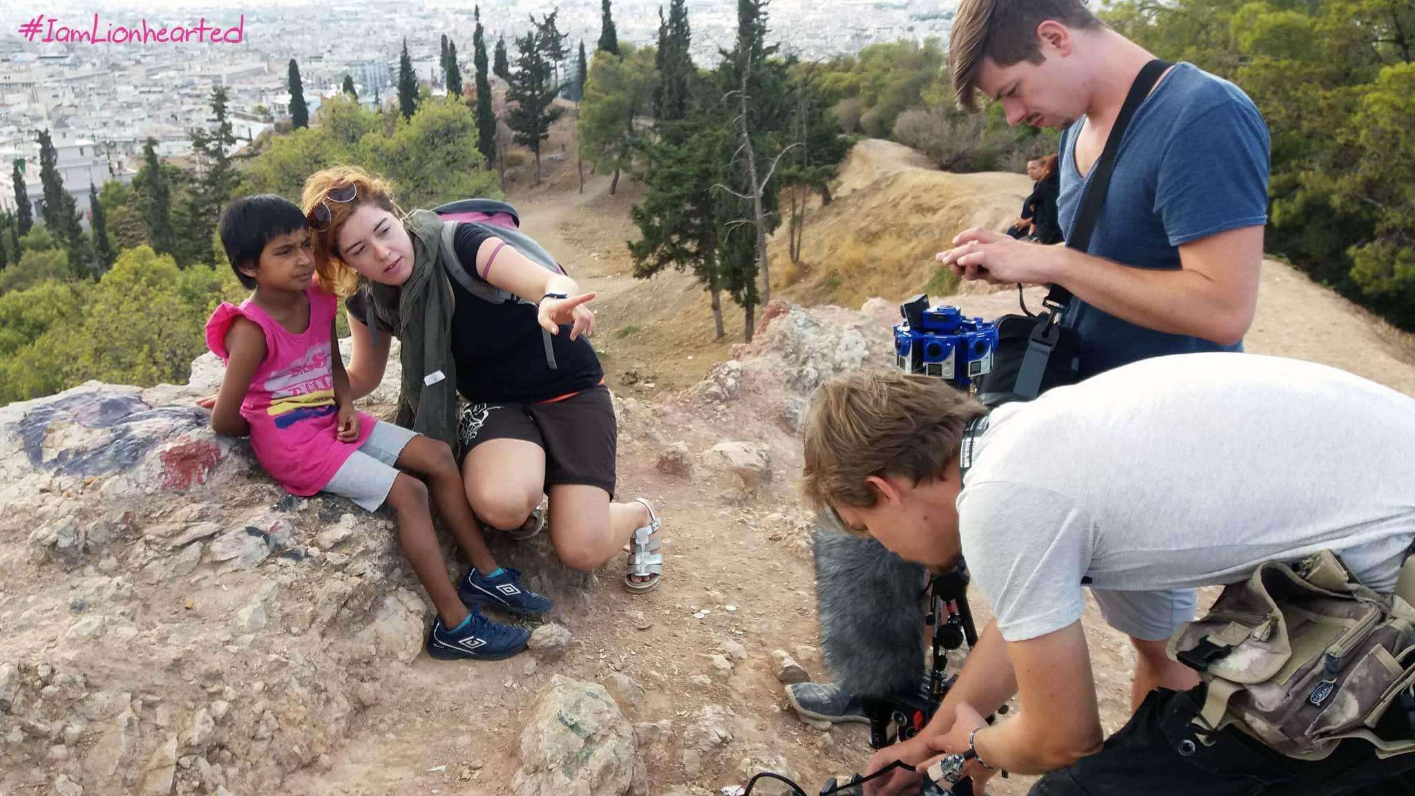 Ricarda erklärt Rida etwas und zeigt auf die Kamera. Das Team und die Kamera stehen vor ihnen.