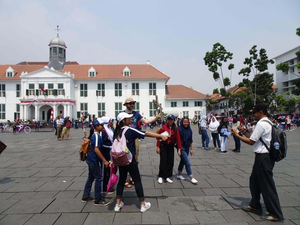 Mein Freund steht auf einem Platz in Jakarta, umringt von Teenies mit Selfiestick, die ein Bild von ihm und seiner 360 Grad Kamera wollen.